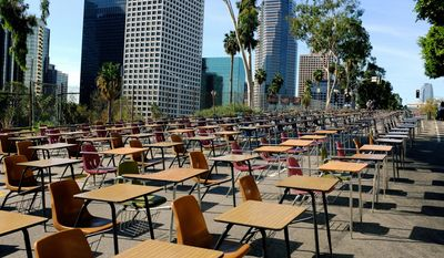 School desks placed by parents, district graduates and activists block a street in front of the Los Angeles Unified School District headquarters in a demonstration against student dropout rates Tuesday, April 8, 2014, in downtown Los Angeles. Protest organizers say the 375 desks are there to represent the 375 students who drop out of the district every week during the school year.  (AP Photo/Richard Vogel)