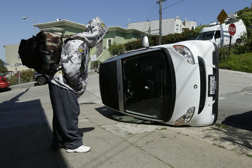 CORRECTS TO PROSPECT AND COSO AVENUES- A man looks at a tipped over Smart car on the corner of Prospect and Coso Avenues in San Francisco, Monday, April 7, 2014. Police in San Francisco are investigating why four Smart cars were flipped over during an apparent early morning vandalism spree. Officer Gordon Shyy, a police spokesman, says the first car was found flipped on its roof and a second was spotted on its side around 1 a.m., Monday in the Bernal Heights neighborhood. (AP Photo/Jeff Chiu)