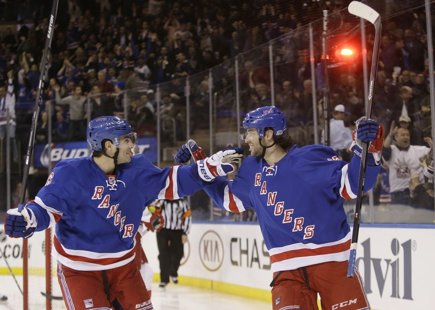 New York Rangers' Benoit Pouliot, right, celebrates with teammate Derick Brassard after scoring a goal during the second period of an NHL hockey game against the Carolina Hurricanes on Tuesday, April 8, 2014, in New York. (AP Photo/Frank Franklin II)
