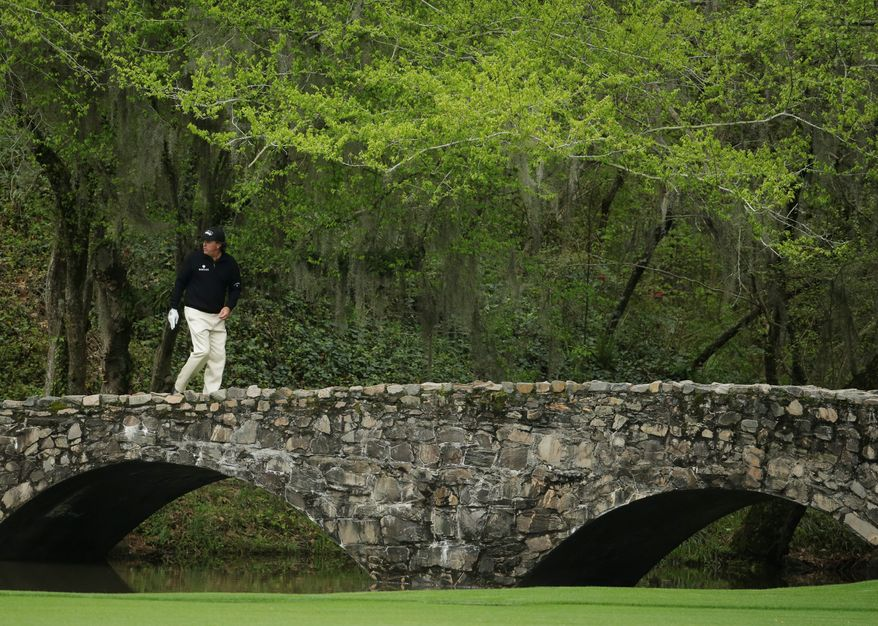 Georgia on their mind: Phil Mickelson takes a familiar walk Tuesday across the Byron Nelson Bridge at the Augusta National Golf Club, where he has won three green jackets in 10 years.