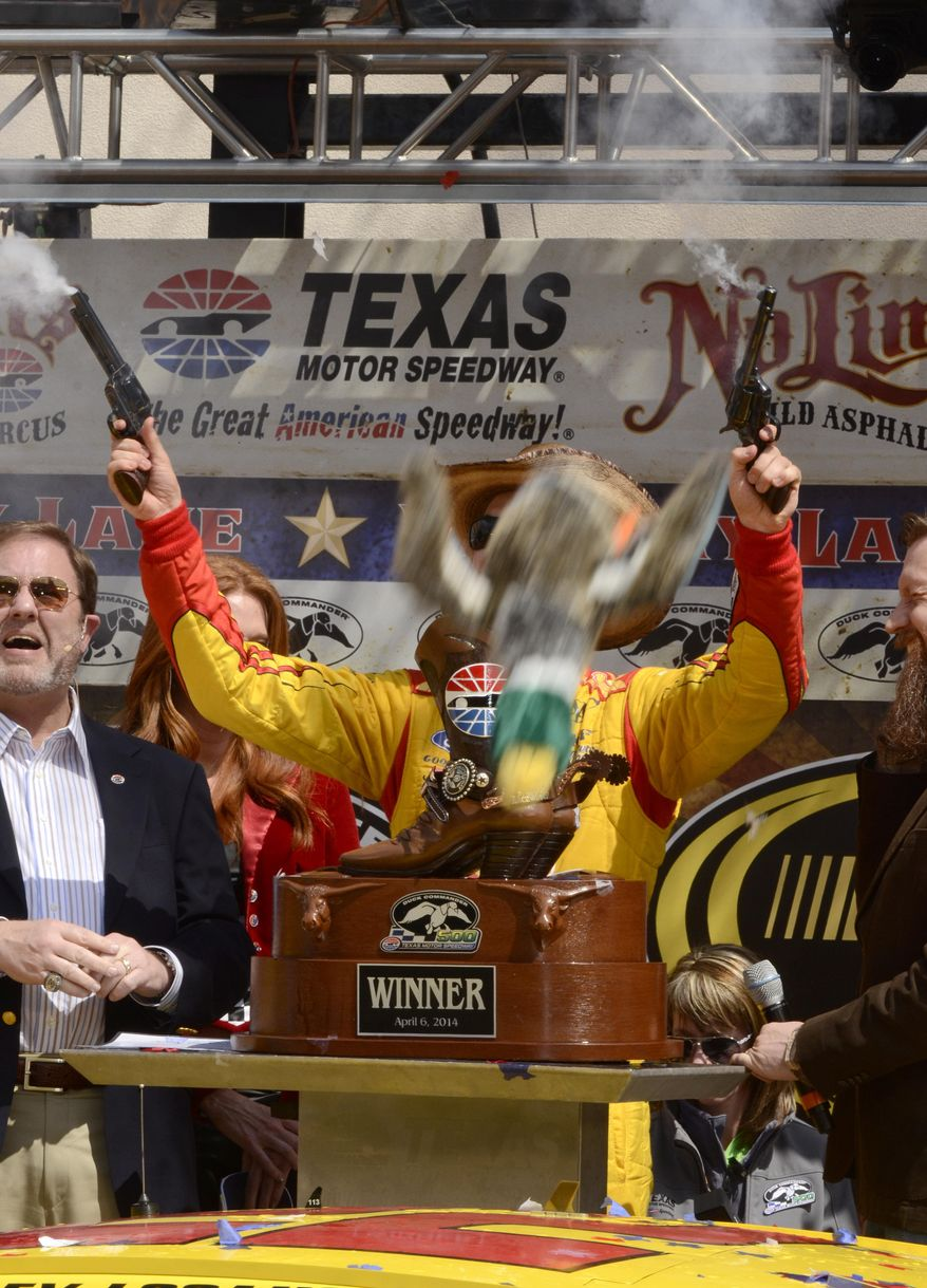 A toy stuffed duck falls in front of Joey Logano as he celebrates in victory lane after winning the NASCAR Sprint Cup Series auto race at Texas Motor Speedway Monday, April 7, 2014, in Fort Worth, Texas. (AP Photo/Larry Papke)