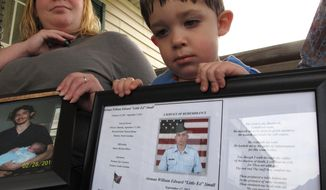 FILE - In this March 18, 2013, file photo, Shane Mercer holds a photo of his father, Airman Will Small, as his mother Alecia Mercer looks on at their home in Kinston, N.C. Small, whose organs were donated to four patients after he died, had at least two untreated raccoon bites several months before he became sick, and tests confirm his rabies-infected kidney led to a Maryland recipient's death. An article in the March 27 issue of Zoonoses and Public Health says social media played an invaluable role in the investigation, allowing officials to find someone who was seated next to the infected donor on a commercial flight in 2011. That person was assessed and not recommended for the shots. (AP Photo/Allen Breed, File)