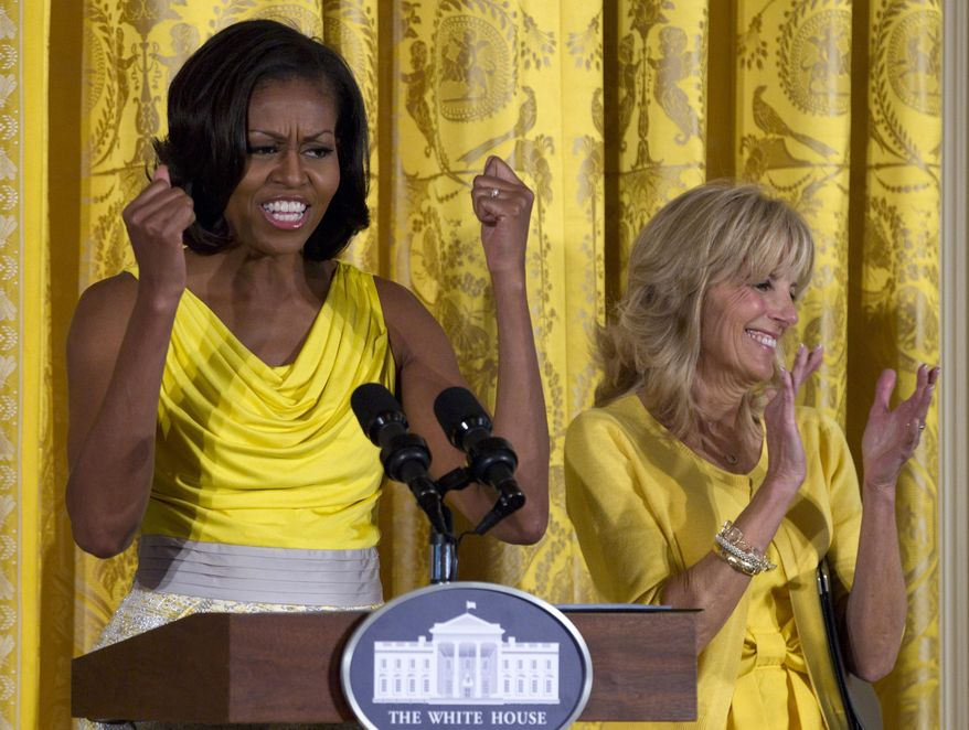FILE - In this May 10, 2012, file photo, first lady Michelle Obama, accompanied by Jill Biden speaks at a Joining Forces event in honor of military mothers in the East Room of the White House in Washington. Michelle Obama and Jill Biden are getting some high-profile support for their initiative to help military families. They are being joined at the White House on Friday by former first lady Rosalynn Carter and former Sen. Elizabeth Dole for an announcement about support for the caregivers of wounded service members and veterans. (AP Photo/Carolyn Kaster, File)
