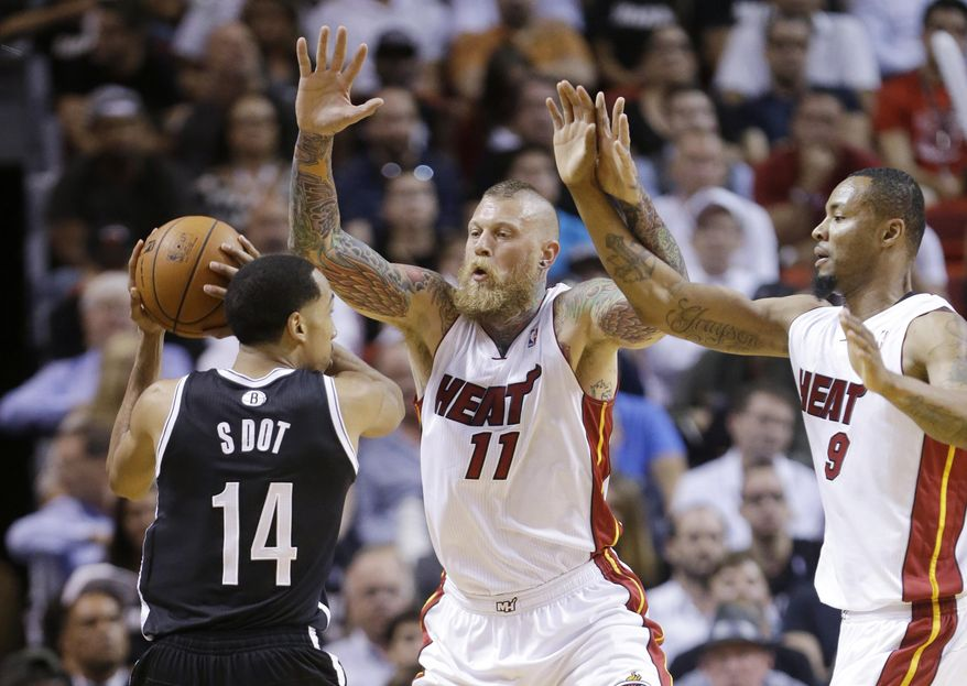 Brooklyn Nets guard Shaun Livingston (14) looks for an open teammate past Miami Heat forward Chris Andersen (11) and forward Rashard Lewis (9) during the first half of an NBA basketball game, Tuesday, April 8, 2014 in Miami. (AP Photo/Wilfredo Lee)
