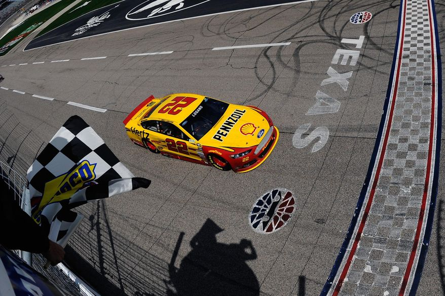 In a photo provided by NASCAR, Joey Logano (22) takes the checked flag winning the NASCAR Sprint Cup Series auto race at Texas Motor Speedway Monday, April 7, 2014 in Fort Worth, Texas.(AP Photo/NASCAR/Jared C. Tilton)