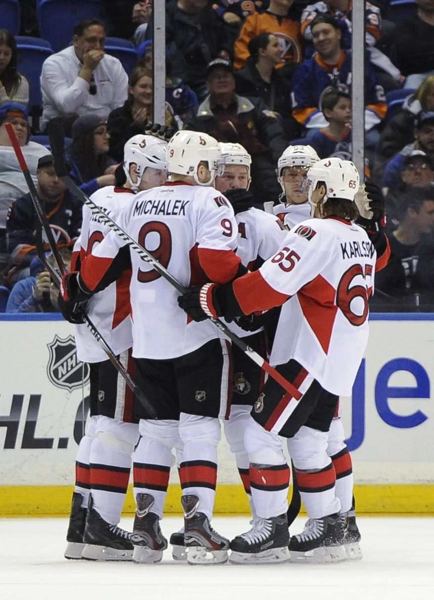Ottawa Senators' Milan Michalek (9), Erik Karlsson (65) and teammates celebrate Jason Spezza's goal against the New York Islanders in the second period of an NHL hockey game Tuesday, April 8, 2014, in Uniondale, N.Y. (AP Photo/Kathy Kmonicek)
