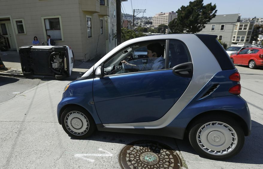 CORRECTS TO PROSPECT AND COSO AVENUES- A woman in a Smart car drives past a tipped over Smart car on the corner of Prospect and Coso Avenues in San Francisco, Monday, April 7, 2014. Police in San Francisco are investigating why four Smart cars were flipped over during an apparent early morning vandalism spree. Officer Gordon Shyy, a police spokesman, says the first car was found flipped on its roof and a second was spotted on its side around 1 a.m. Monday in the Bernal Heights neighborhood. (AP Photo/Jeff Chiu)