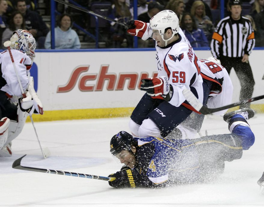 St. Louis Blues' T.J. Oshie (74) slides across the ice as he trips up Washington Capitals' Julien Brouillette (59) during the second period of an NHL hockey game, Tuesday, April 8, 2014, in St. Louis.(AP Photo/Tom Gannam)
