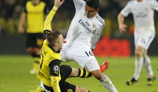Dortmund's Marco Reus, left, and Real's Casemiro challenge for the ball during the Champions League quarterfinal second leg soccer match between Borussia Dortmund and Real Madrid in the Signal Iduna stadium in Dortmund, Germany, Tuesday, April 8, 2014. (AP Photo/Frank Augstein)