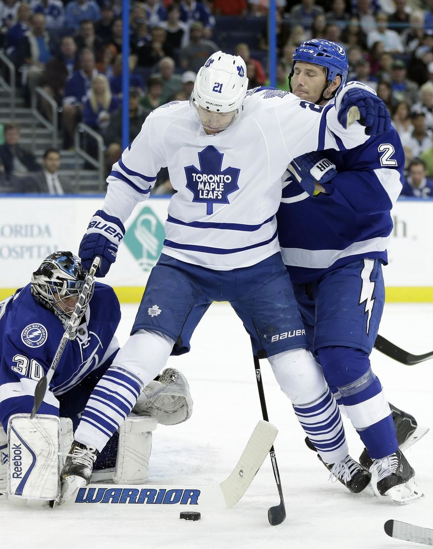 Toronto Maple Leafs left wing James van Riemsdyk (21) tries to control a loose puck in front of Tampa Bay Lightning defenseman Eric Brewer (2) and goalie Ben Bishop during the first period of an NHL hockey game Tuesday, April 8, 2014, in Tampa, Fla. (AP Photo/Chris O'Meara)
