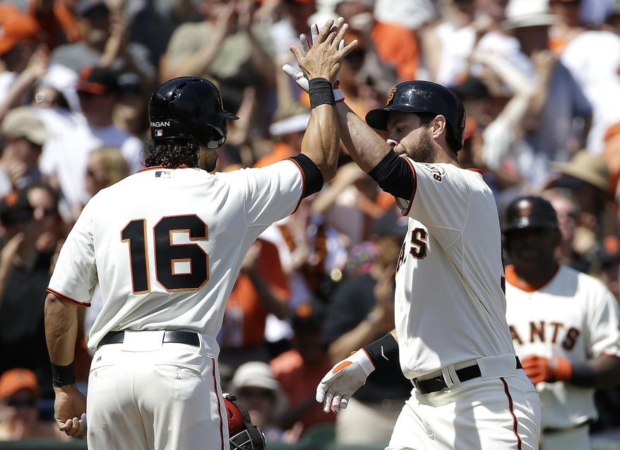 San Francisco Giants' Brandon Belt, right, is congratulated by Angel Pagan after hitting a two-run home run off of Arizona Diamondbacks pitcher Trevor Cahill that scored Pagan during the first inning of the home opener MLB National League baseball game in San Francisco, Tuesday, April 8, 2014. (AP Photo/Eric Risberg)