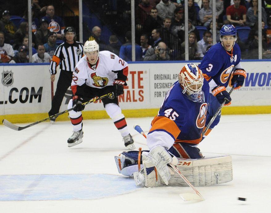 New York Islanders goalie Anders Nilsson (45) turns away a shot as teammate Travis Hamonic (3) and Ottawa Senators' Erik Condra (22) watch during the first period of an NHL hockey game Tuesday, April 8, 2014, in Uniondale, N.Y. (AP Photo/Kathy Kmonicek)