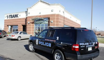 **FILE** Police officers work around a bank that was robbed in the north Denver suburb of Westminster, Colo., on Nov. 19, 2009. (Associated Press)