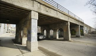 An automobile travels under one of two railroad viaducts on Cass Ave., in Detroit, Tuesday, April 8, 2014. Proposals for a project to transform the undersides of two railroad viaducts have been submitted from as far afield as Europe and Asia, as well as North America, organizers said. Proposals accepted by the Midtown Viaducts Public Art and Light Project will be funded up to $75,000 per viaduct. The project is organized by Midtown Detroit Inc., a nonprofit planning and development organization that works in the area. The application deadline is April 30. (AP Photo/Carlos Osorio)