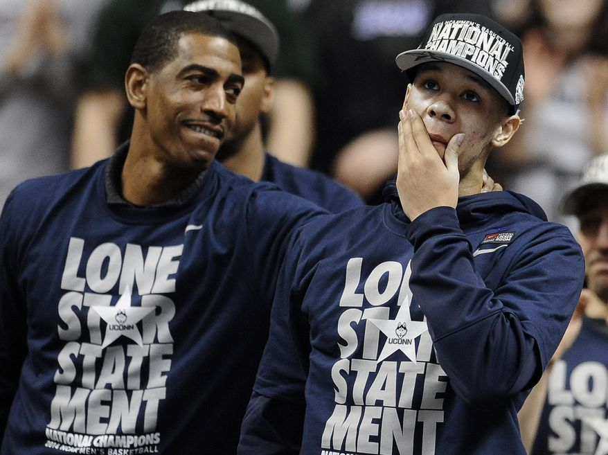 Connecticut's Shabazz Napier, right, reacts as his name is revealed on the Huskies Wall of Honor as coach Kevin Ollie, left, looks over at Napier during a pep rally celebrating Connecticut's fourth NCAA men's basketball championship Tuesday, April 8, 2014, in Storrs, Conn. (AP Photo/Jessica Hill)