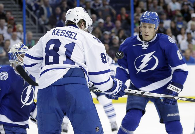 Toronto Maple Leafs right wing Phil Kessel (81) tries to control a flying puck in front of Tampa Bay Lightning defenseman Sami Salo (6), of Finland, during the first period of an NHL hockey game Tuesday, April 8, 2014, in Tampa, Fla. (AP Photo/Chris O'Meara)
