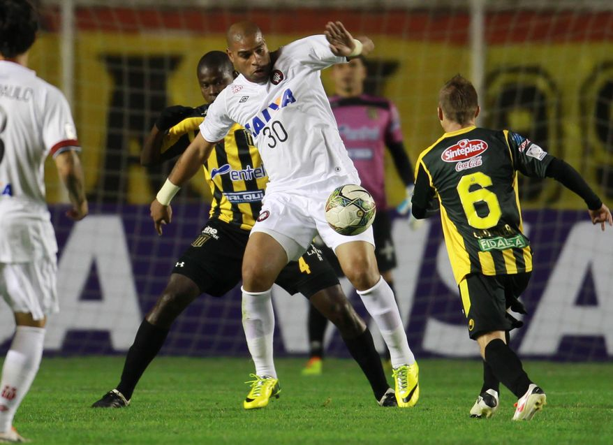 Adriano of Brazil's Atletico Paranaense, front center, fights for the ball with Jefferson Lopes of Bolivia's The Strongest, behind left, at a Copa Libertadores soccer match in La Paz, Bolivia, Tuesday, April 8, 2014. (AP Photo/Juan Karita)