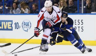 St. Louis Blues defenseman Alex Pietrangelo , right, competes for the puck against Washington Capitals right wing Tom Wilson during the third period of an NHL hockey game Tuesday, April 8, 2014, in St. Louis. The Capitals won 4-1. (AP Photo/St. Louis Post-Dispatch, Chris Lee) EDWARDSVILLE OUT  ALTON OUT