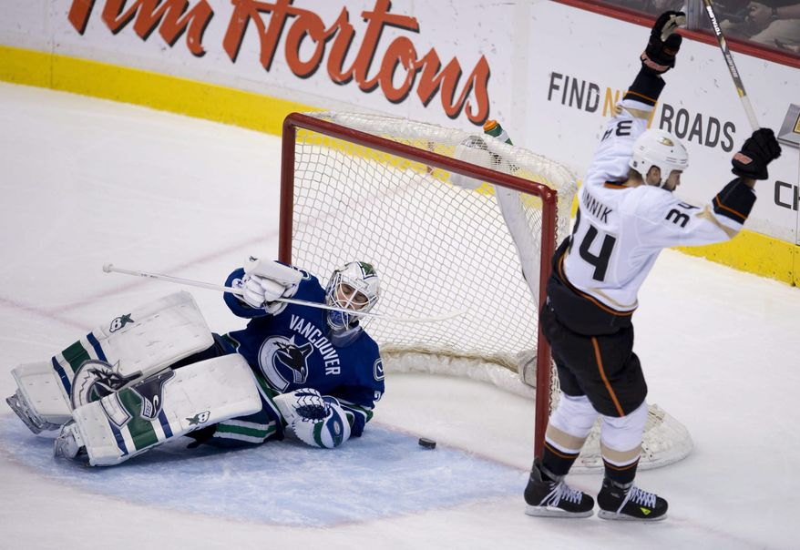Anaheim Ducks right wing Daniel Winnik (34) celebrates his goal past Vancouver Canucks goalie Eddie Lack (31) during the first period of NHL action in Vancouver, British Columbia, on Monday, April 7, 2014. (AP Photo/The Canadian Press, Jonathan Hayward)