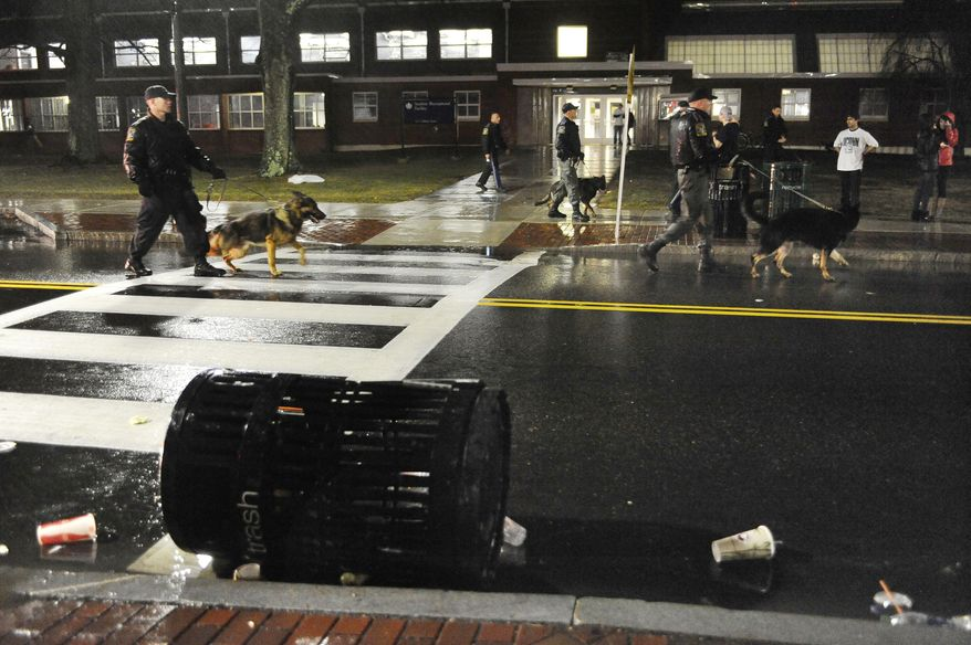 Connecticut State Police use dogs to move clear students from an area they had gathered to celebrate their team's 60-54 victory over Kentucky in the NCAA Final Four tournament college basketball championship game, Monday, April 7, 2014, in Storrs, Conn. (AP Photo/Jessica Hill)