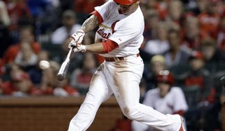 St. Louis Cardinals' Kolten Wong hits a two-run triple during the second inning of a baseball game against the Cincinnati Reds on Tuesday, April 8, 2014, in St. Louis. (AP Photo/Jeff Roberson)