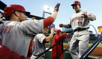 Cincinnati Reds' Joey Votto, right, is congratulated by teammate Zack Cozart, left, after scoring on a two-run triple by Jay Bruce during the first inning of a baseball game against the St. Louis Cardinals on Tuesday, April 8, 2014, in St. Louis. (AP Photo/Jeff Roberson)