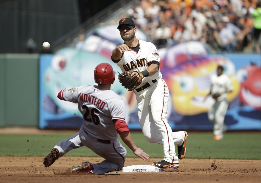 San Francisco Giants second baseman Brandon Hicks, rear, throws to first base after forcing out Arizona Diamondbacks' Miguel Montero (26) at second base on Mark Trumbo's fielders choice during the second inning of the home opener MLB National League baseball game in San Francisco, Tuesday, April 8, 2014. (AP Photo/Eric Risberg)
