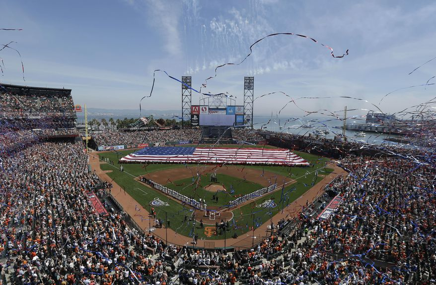 A large flag is presented in the AT&T Park outfield during the national anthem before the home opener MLB National League baseball game between the San Francisco Giants and the Arizona Diamondbacks in San Francisco, Tuesday, April 8, 2014. (AP Photo/Jeff Chiu)
