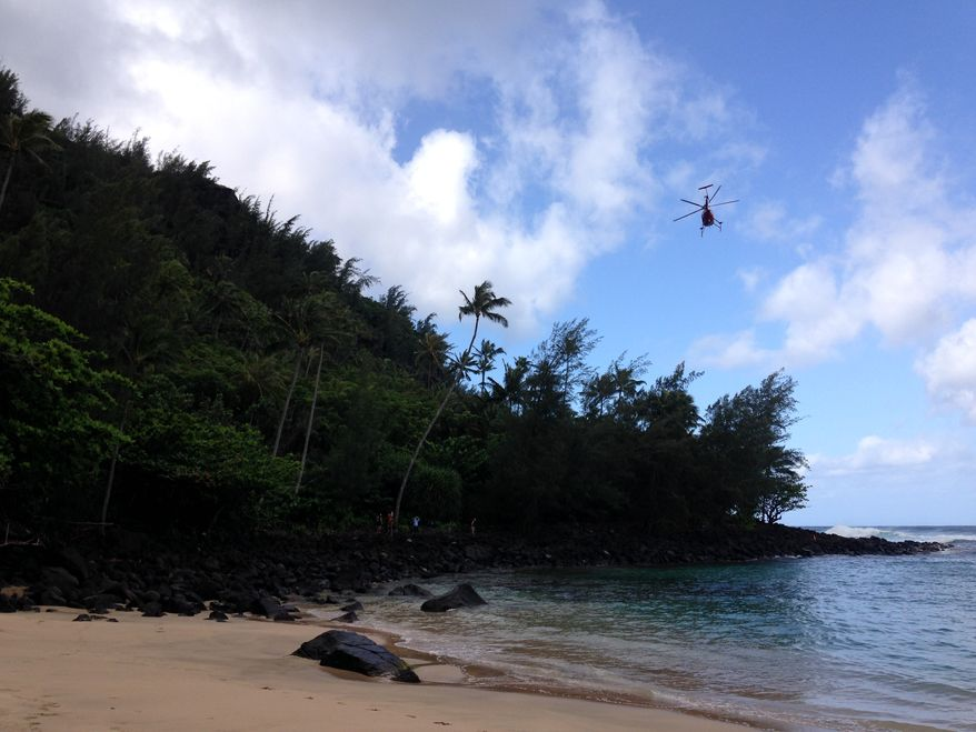 A Kauai County Fire Department helicopter flies along Kauai's Napali Coast to rescue hikers stranded by rising waters crossing a trail in Kapaa, Hawaii, on Monday, April 7, 2014. (AP Photo/Rachel La Corte)