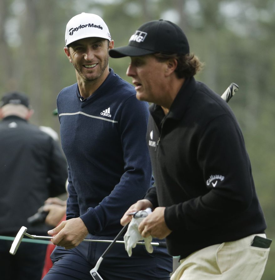 Dustin Johnson, left, walks with Phil Mickelson on the third fairway during a practice round for the Masters golf tournament Tuesday, April 8, 2014, in Augusta, Ga. (AP Photo/Chris Carlson)