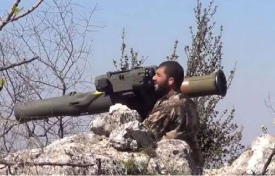 ** FILE ** A Syrian rebel uses a  TOW missile. (Harakat Hazm)