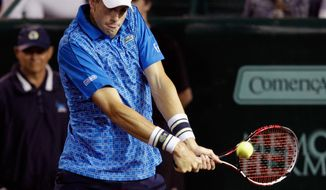 John Isner, of the United States, hits a return to Dustin Brown, of Germany, at the U.S. Men's Clay Court Championship tennis tournament, Wednesday, April 9, 2014, in Houston. (AP Photo/Houston Chronicle, Bob Levey) MANDATORY CREDIT