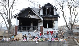 In this April 8, 2014 photo, stuffed animals line a wall in front of a burned home in Detroit. In an announcement Wednesday by Mayor Mike Duggan, the city of Detroit plans to post legal notices and take court action if needed for owners of blighted properties. (AP Photo/Detroit News, Robin Buckson)  DETROIT FREE PRESS OUT; HUFFINGTON POST OUT