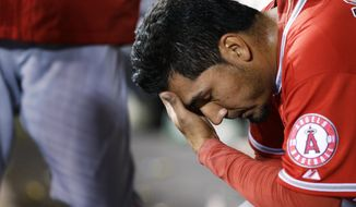 Los Angeles Angels pitcher Fernando Salas sits in the dugout after he was pulled in the seventh inning of a baseball game after giving up a solo home run to Seattle Mariners' Corey Hart, Tuesday, April 8, 2014, in Seattle. (AP Photo/Ted S. Warren)