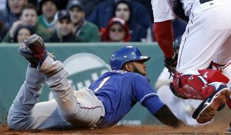 Texas Rangers' Elvis Andrus slides into home to score on a sacrifice fly hit by Alex Rios in the eighth inning of a baseball game against the Boston Red Sox at Fenway Park in Boston, Wednesday, April 9, 2014. (AP Photo/Elise Amendola)