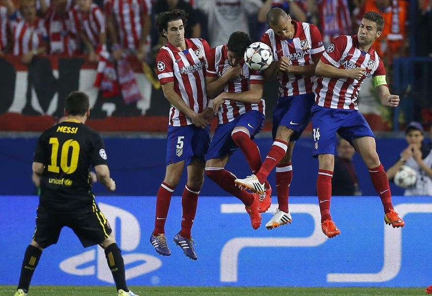 Barcelona's Lionel Messi kicks the ball in front of Atletico players during the Champions League quarterfinal second leg soccer match between Atletico Madrid and FC Barcelona at the Vicente Calderon stadium in Madrid, Spain, Wednesday, April 9, 2014. (AP Photo/Andres Kudacki)