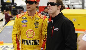 FILE - In this April 7, 2014 file photo, Joey Logano, left,  and Brad Keselowski stand on the track before the start of the NASCAR Sprint Cup Series auto race at Texas Motor Speedway in Fort Worth, Texas. As he chased Logano around Texas Motor Speedway, more than a few people openly wondered if Keselowski wasn't letting off the gas just a little bit in an intentional effort to allow his teammate to win. (AP Photo/Ralph Lauer, File)