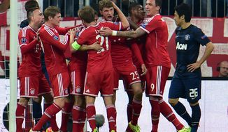 Bayern's scorer Thomas Mueller, center, and his teammates celebrate their side's 2nd goal during the Champions League quarterfinal second leg soccer match between Bayern Munich and Manchester United in the Allianz Arena in Munich, Germany, Wednesday, April 9, 2014. (AP Photo/Kerstin Joensson)