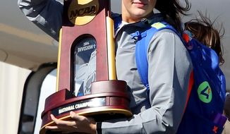 Connecticut's Stephanie Dolson waves to fans while carrying the NCAA National Championship Trophy at Bradley International Airport in Windsor Locks, Conn., Wednesday, April 9, 2014, the day after the Huskies defeated Notre Dame to clinch their ninth national championship. (AP Photo/Journal Inquirer, Jared Ramsdell)  MANDATORY CREDIT
