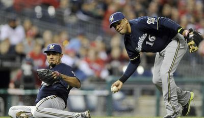 Milwaukee Brewers' third baseman Aramis Ramirez (16) picks up a ball bunted by Philadelphia Phillies' Ben Revere as Brewers' Matt Garza slides out the way during the fourth inning of a baseball game on Wednesday, April 9, 2014, in Philadelphia. (AP Photo/Michael Perez)