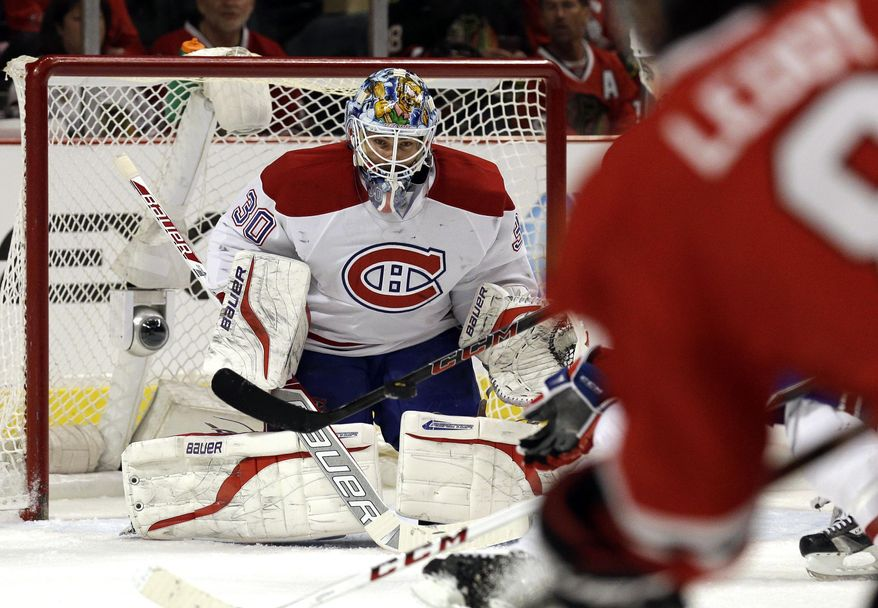 Montreal Canadiens goalie Peter Budaj (30) saves a shot by Chicago Blackhawks' Nick Leddy (8) during the second period of an NHL hockey game in Chicago, Wednesday, April 9, 2014. (AP Photo/Nam Y. Huh)