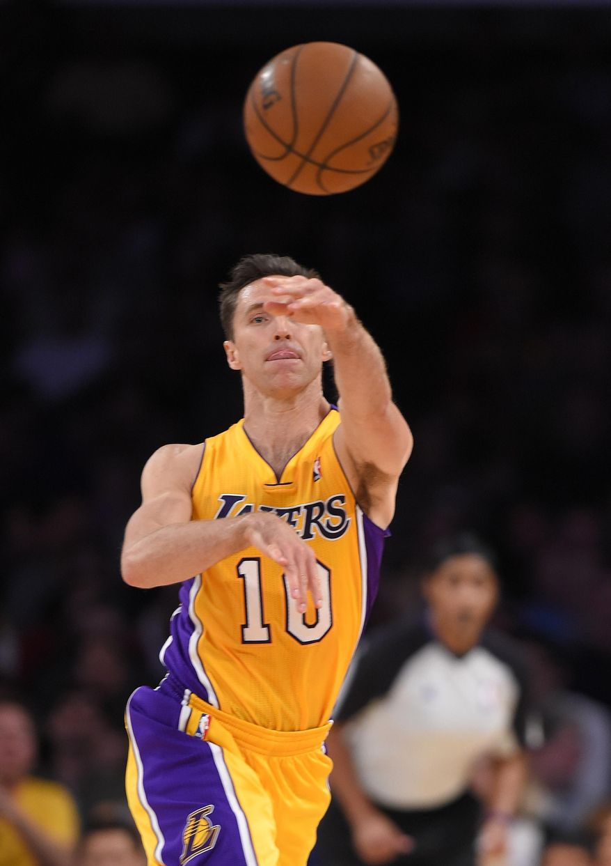 Los Angeles Lakers' Steve Nash passes the ball for an assist to tie for third place for career assists, during the first half of the Lakers' NBA basketball game against the Houston Rockets, Tuesday, April 8, 2014, in Los Angeles. (AP Photo/Mark J. Terrill)