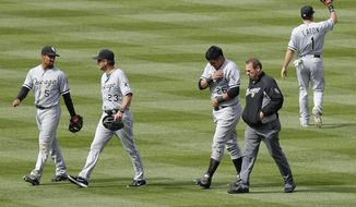 Chicago White Sox athletic trainer Herman Schneider, second from right, escorts Avisail Garcia (26) off the field after Garcia jammed his left shoulder on a diving catch during the sixth inning of a baseball game against the Colorado Rockies, Wednesday, April 9, 2014, in Denver. The Rockies won 10-4. (AP Photo/Barry Gutierrez)