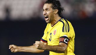 "FILE - In this Oct. 15, 2013, file photo, Colombia's Mario Yepes celebrates after scoring his second goal against Paraguay during a 2014 World Cup qualifying soccer match  in Asuncion, Paraguay. The ""Coffee Growers"" ripped through qualification, hammering Uruguay 4-0 on their way to earning 30 points from 16 matches. Falcao sealed qualification with two late goals against Chile, coming from behind for a 3-3 home draw. (AP Photo/Victor R. Caivano, File)"
