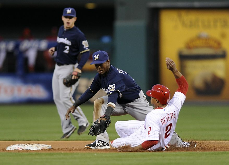 Philadelphia Phillies' Ben Revere, right, slides into second base and tries to beat a tag from Milwaukee Brewers shortstop Jean Segura during the first inning of a baseball game on Wednesday, April 9, 2014, in Philadelphia. (AP Photo/Michael Perez)