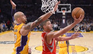 Houston Rockets forward Chandler Parsons, right, shoots as Los Angeles Lakers center Robert Sacre defends during the first half of an NBA basketball game, Tuesday, April 8, 2014, in Los Angeles. (AP Photo/Mark J. Terrill)