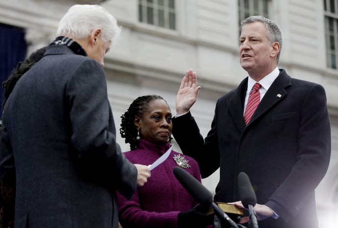 FILE - In this Jan. 1, 2014, file photo, Mayor-elect Bill de Blasio, right, takes the oath of office administered by former President Bill Clinton, left, while de Blasio's wife, Chirlane McCray, center, holds the bible for her husband during his public inauguration ceremony at City Hall in New York. De Blasio's first 100 days as mayor of New York City were marked in nearly equal measures by accomplishing campaign goals and committing political blunders. (AP Photo/Seth Wenig, File)