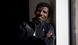 Former marathon world record holder Ethiopia's Haile Gebrselassie, aged 40, who will be the pacemaker for the elite men's runners at the London Marathon, poses for photographers at a hotel in London, Wednesday, April 9, 2014.  The London marathon takes place on Sunday.  (AP Photo/Matt Dunham)