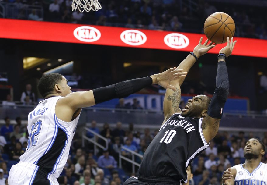 Brooklyn Nets' Marcus Thornton (10) takes a shot as he is fouled by Orlando Magic's Tobias Harris (12) during the first half of an NBA basketball game in Orlando, Fla., Wednesday, April 9, 2014. (AP Photo/John Raoux)