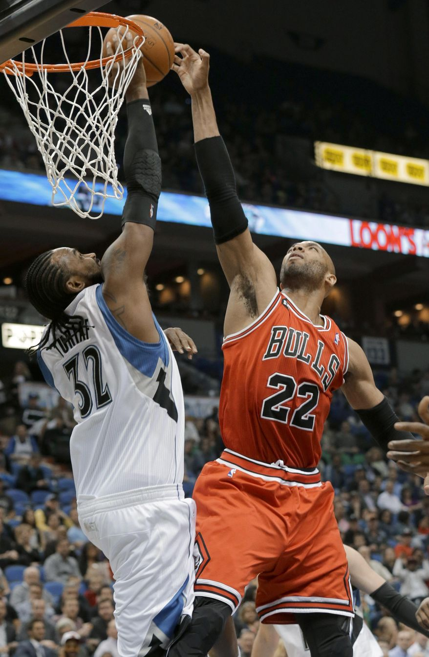 Minnesota Timberwolves center Ronny Turiaf (32) blocks a shot by Chicago Bulls forward Taj Gibson (22) during the second quarter of an NBA basketball game in Minneapolis, Wednesday, April 9, 2014. (AP Photo/Ann Heisenfelt)